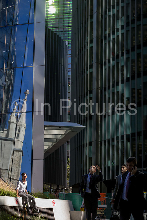 Londoners enjoy the sunshine with the reflection of the church of St. Mary Axe and financial services offices in the City of London, the capitals historic financial district, on 2nd August 2018, in London, England.