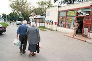 A couple of spry shoppers walking down Lutomierska Street Balucki District Lodz Central Poland