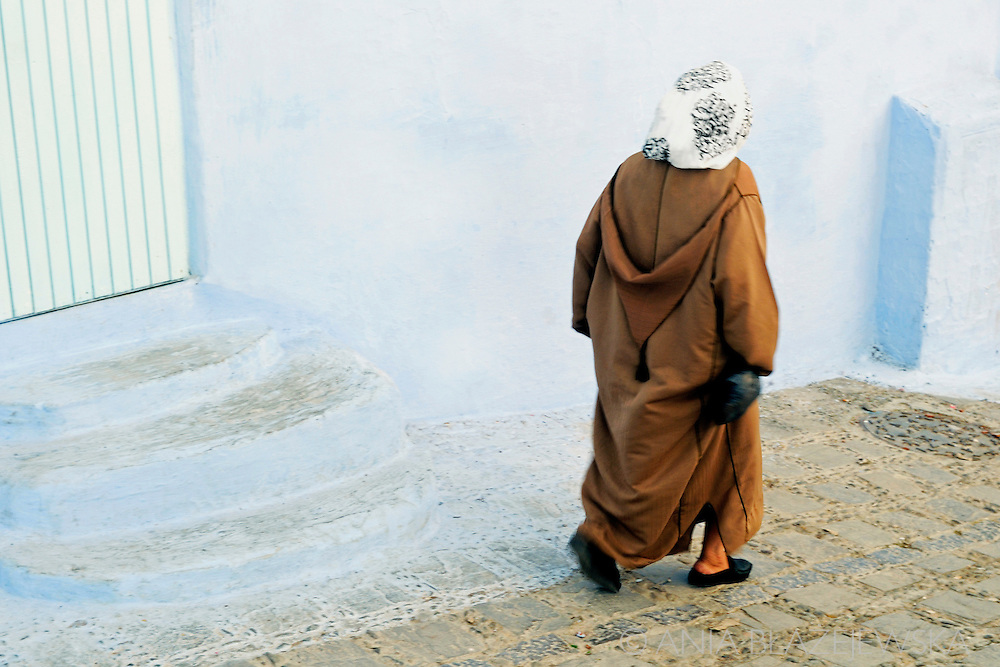 Morocco, Chefchaouen. Woman in jellaba walking the street of the blue medina.
