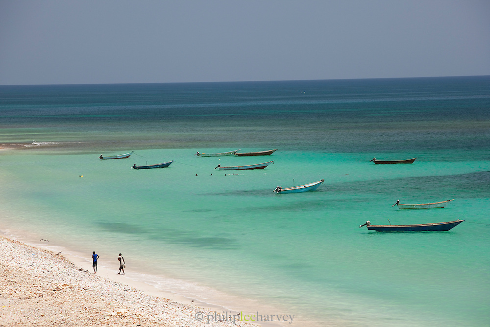 Fishing boats and fishing men moored in the shores of Qalansia, Socotra, Yemen