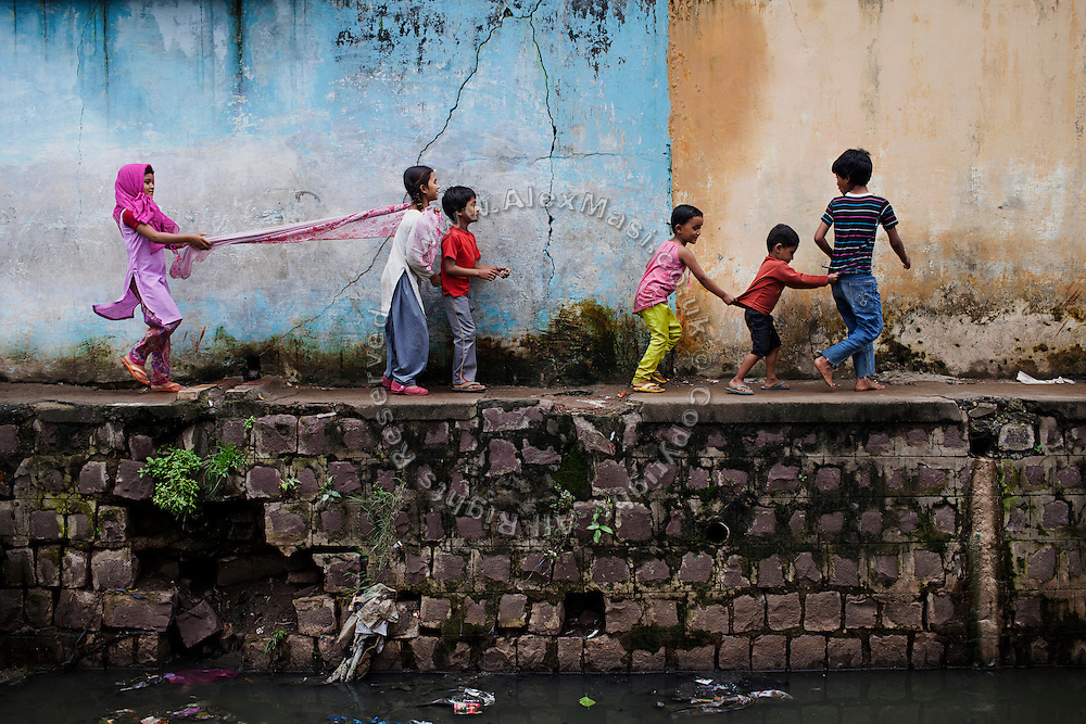 Children are playing along a municipal drain in Kasi Camp, one of the water-affected colonies near the abandoned Union Carbide (now DOW Chemical) industrial complex in Bhopal, Madhya Pradesh, India, site of the infamous 1984 gas tragedy. The poisonous cloud that enveloped Bhopal left everlasting consequences that today continue to consume people's lives.