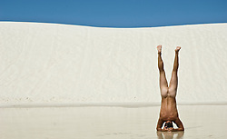 naked man doing a handstand in White Sands, New Mexico