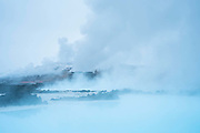Steam hangs over the blue water from the thermal ponds created by the power station at Svartsengi. The Blue Lagoon, Iceland.