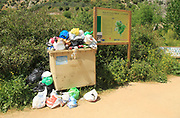 Overflowing rubbish bin at natural park, Cueva del Gato, Benaojan, Serrania de Ronda, Malaga province, Spain