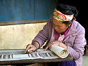 Nan Ya, a Hmong Leng ethnic minority woman decorates the woven hemp fabric by batik, a wax resist technique, Thien Pha, Houaphan province, Lao PDR. Bees' wax is collected from the forest, heated in small metal pots and mixed with indigo paste (which colours the wax and makes it easier to see on the cloth). A bamboo pen with a metal nib is used for drawing the wax onto the hemp. The wax marks will resist the dye when the cloth is dipped in the indigo dye bath and left to dry. After the last dye bath has been completed, the cloth is boiled to remove the wax. The resulting fabric is an indigo blue colour with white designs and is the base for cotton applique and colourful embroidery. Making hemp fabric is a long and laborious process which the Hmong women make into skirts for their traditional clothing. In Lao PDR, hemp is now only cultivated in remote mountainous areas of the north.