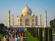 The Taj Mahal at sunrise with the crowds of tourists. It is an ivory-white marble mausoleum on the southern bank of the river Yamuna