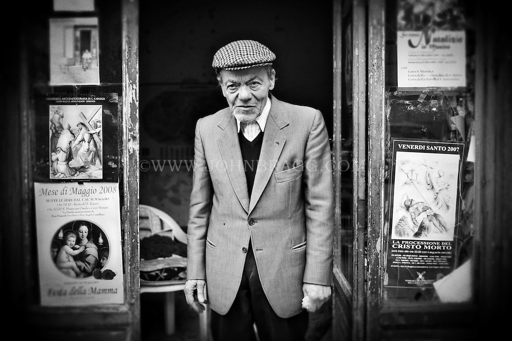 Black and white photo of an old man standing in a doorway in Sorrento, Italy.