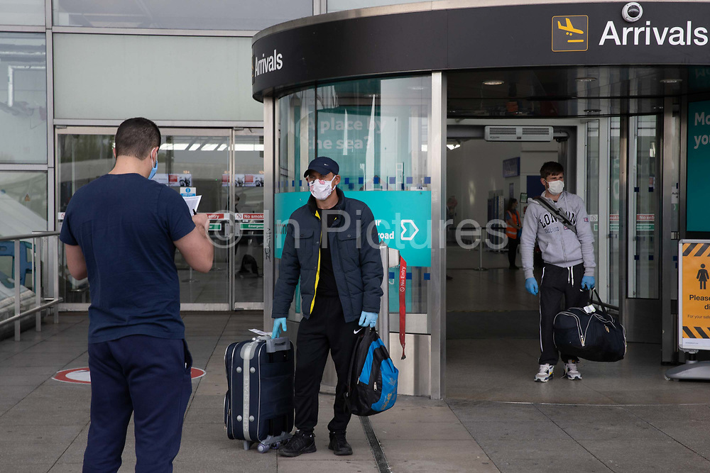 A chartered plane with Romanian seasonal workers arrives at London Stanstead Airport to fill the shortfall in workers to pick fruit and vegetables from British farms on the 16th April 2020, in London, United Kingdom. Staff awaited the workers to register them. The planes were chartered by large fruit and veg producers such as Gs Fresh, who have been trying but struggling to meet a large labour gap for fruit and veg picking on UK farms as a result of the Covid-19 / Coronavirus crisis / Pandemic.