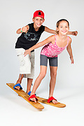Indoor playground  2 children aged 8-12 attempt to walk together on wooden walking skies On white Background