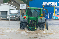 © Licensed to London News Pictures. 16/02/2020.  Builth Wells, Powys, Wales, UK. A tractor goes on a rescue mission. The river Wye bursts it's banks at Builth Wells in Powys, Wales, UK. after heavy rainfall yesterday and last night, causing the A483 road to be closed and traffic diverted. The river level broke the all-time high (5.05 m) at 08.30hrs  this morning at Builth Wells. According to Natural Resources Wales the highest recorded level at Builth Wells was 4.95m on 28/10/98 at 2:45 am (GMT) Photo credit: Graham M. Lawrence/LNP