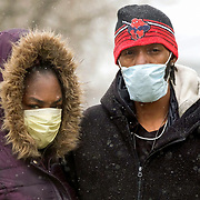 Lashonda Walker, left, and Lavell Hutcherson, both of Toledo, pose for a portrait in their masks in the light snow on 13th Street in Toledo on Wednesday, April 15, 2020. THE BLADE/KURT STEISS