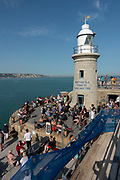 A busy day for people hanging out at the Harbour Arm in Folkestone, England, United Kingdom. Folkestone is a port town on the English Channel, in Kent, south-east England. The town lies on the southern edge of the North Downs and was an important harbour and shipping port for most of the 19th and 20th centuries.
