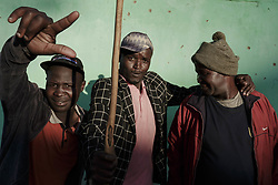 December 8, 2017 - Matatiele, Eastern Cape, South Africa - Three friends drink alcohol in the early evening outside a bar. Alcohol plays a big part of daily life at the Eastern Cape. Alcohol consumption is very normal and often explained as part of the culture. However, the alcohol consumed is no longer homemade traditional beer but strong and expensive liquor, which is enjoyed by many on a daily basis. People would often go without food for the entire day, but spend money on alcohol. (Credit Image: © Stefan Kleinowitz/ZUMA Wire)