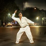 Men dancing Bollywood indian dances in the street.