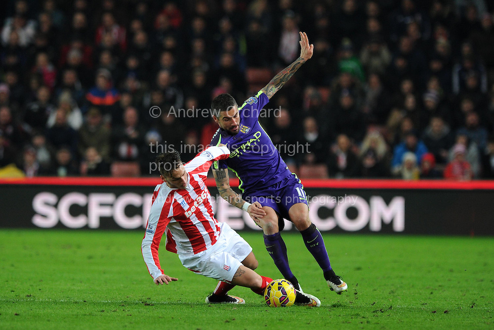 Aleksandar Kolarov of Manchester city is tackled by Stoke city's Marko Arnautovic . Barclays Premier League match, Stoke city v Manchester city at the Britannia Stadium in Stoke on Trent , Staffs on Wed 11th Feb 2015.<br /> pic by Andrew Orchard, Andrew Orchard sports photography.