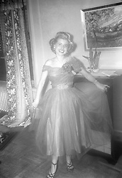 Woman in a formal evening dress posing in her living room