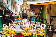 "26 APRIL 2013 - BANGKOK, THAILAND:    A ""spirit house"" on a narrow soi (street or alley) in Talat Noi. A spirit house is a shrine to the protective spirit of a place that are found in the Southeast Asian countries of Burma, Cambodia, Laos, and Thailand. The Talat Noi neighborhood in Bangkok started as a blacksmith's quarter. As cars and buses replaced horse and buggy, the blacksmiths became mechanics and now the area is lined with car mechanics' shops. It is one the last neighborhoods in Bangkok that still has some original shophouses and pre World War II architecture. It is also home to a  Teo Chew Chinese emigrant community.      PHOTO BY JACK KURTZ"