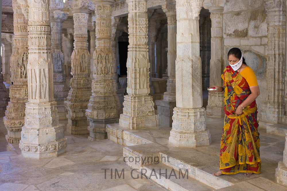 Jain pilgrim with traditional mask carrying offering at The Ranakpur Jain Temple at Desuri Tehsil in Pali District, Rajasthan, India