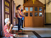 15 FEBRUARY 2015 - BANGKOK, THAILAND: A woman sits on the floor with her rosary at Santa Cruz Catholic Church in the Kudeejeen neighborhood in Bangkok. Santa Cruz church was established in 1770  and is one of the oldest and most historic Catholic churches in Thailand. The church was originally built by Portuguese soldiers allied with King Taksin the Great. Taksin authorized the church as a thanks to the Portuguese who assisted the Siamese during the war with Burma. Most of the Catholics in the neighborhood trace their family roots to the original Portuguese soldiers who married Siamese (Thai) women. There are about 300,000 Catholics in Thailand in about 430 Catholic parishes and about 660 Catholic priests in Thailand. Thais are tolerant of other religions and although Thailand is officially Buddhist, Catholics are allowed to freely practice and people who convert to Catholicism are not discriminated against.      PHOTO BY JACK KURTZ