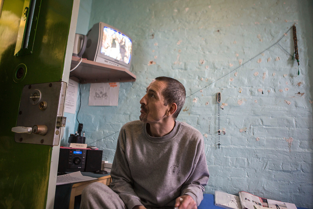 A prisoner sitting on the bed in his cell talking to an officer at the door. HMP/YOI Portland, Dorset. A resettlement prison with a capacity for 530 prisoners. Portland, Dorset, United Kingdom.