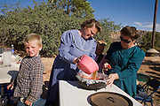 "Aug 9, 2008 -- COLORADO CITY, AZ: Members of the Jessop family make fruit cobbler during a family picnic near the family's home in Colorado City, AZ. Colorado City and neighboring town of Hildale, UT, are home to the Fundamentalist Church of Jesus Christ of Latter Day Saints (FLDS) which split from the mainstream Church of Jesus Christ of Latter Day Saints (Mormons) after the Mormons banned plural marriage (polygamy) in 1890 so that Utah could gain statehood into the United States. The FLDS Prophet (leader), Warren Jeffs, has been convicted in Utah of ""rape as an accomplice"" for arranging the marriage of teenage girl to her cousin and is currently on trial for similar, those less serious, charges in Arizona. After Texas child protection authorities raided the Yearning for Zion Ranch, (the FLDS compound in Eldorado, TX) many members of the FLDS community in Colorado City/Hildale fear either Arizona or Utah authorities could raid their homes in the same way. Older members of the community still remember the Short Creek Raid of 1953 when Arizona authorities using National Guard troops, raided the community, arresting the men and placing women and children in ""protective"" custody. After two years in foster care, the women and children returned to their homes. After the raid, the FLDS Church eliminated any connection to the ""Short Creek raid"" by renaming their town Colorado City in Arizona and Hildale in Utah. A member of the Jessop family weeds the community corn plot in Colorado City, AZ. The Jessops are a polygamous family and members of the FLDS. Photo by Jack Kurtz / ZUMA Press"