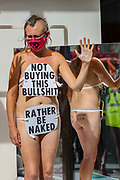 An Extinction Rebellion activist who glued themselves to the shop window of H&M in Oxford street in London looks at the members of the public passing by and greeting them on Wednesday, Sept 9, 2020. The activists are completely naked, except for strategically placed placards that made a statement about social and environmental injustice in the fashion industry. The signs read 'Fashion is F*cked, Rather Be Naked', 'Won't Wear Injustice, Rather be Naked' and 'Not Buying This Bullshit, Rather Be Naked'. Environmental nonviolent activists group Extinction Rebellion enters its 9th day of continuous ten days protests to disrupt political institutions throughout peaceful actions swarming central London into a standoff, demanding that central government obeys and delivers Climate Emergency bill. (VXP Photo/ Vudi Xhymshiti)
