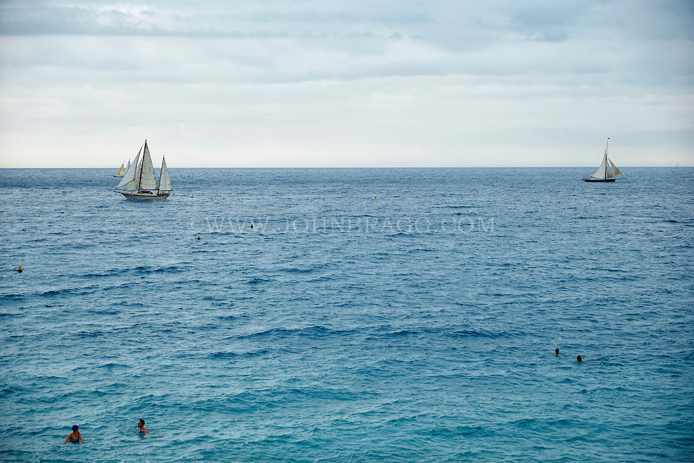 View of swimmers and sailboats luxuriating in the Mediterranean Sea, Nice, France.