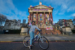 © Licensed to London News Pictures. 13/11/2020. LONDON, UK. A cyclist takes a selfie in front of the new Winter Commission at Tate Britain unveiled by British artist Chila Kumari Singh Burman.  Her installation on the façade references mythology, Bollywood, radical feminism, political activism and family memories in a celebration of neon light and swirling colour and is on display until 31 January 2021.  Photo credit: Stephen Chung/LNP
