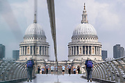 With the dome of St Paul's cathedral in the distance, pedestrians cross the river Thames on the Millennium Bridge, on 24th June 2021, in London, England. London's newest river crossing for 100-plus years coincided with the Millennium. It was hurriedly finished and opened to the public on 10 June 2000 when an estimated 100,000 people crossed it to discover the structure oscillated so much that it was forced to close 2 days later. Over the next 18 months designers added dampeners to stop its wobble but it already symbolised what was embarrassing and failing in British pride. Now the British Standard code of bridge loading has been updated to cover the swaying phenomenon, referred to as 'Synchronous Lateral Excitation'. CREDIT RICHARD BAKER.