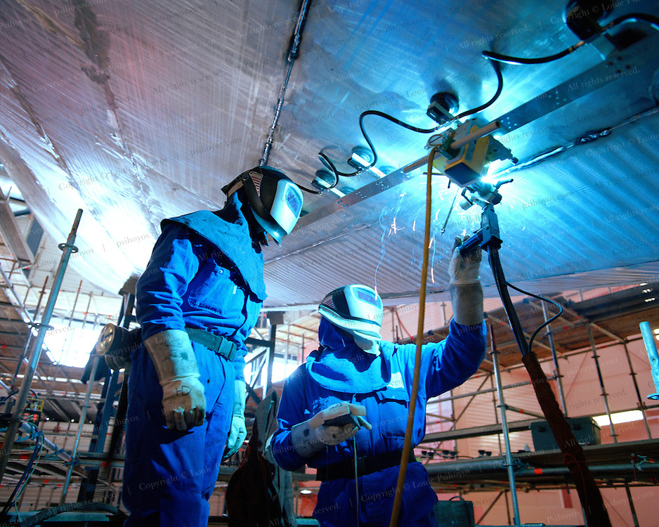 Welding under the Hull of Athena, a three masted schooner, currently being built by the Royal Huisman Shipyard of Vollenhove, Holland.