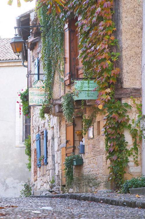 A cobble stone street and old cross beam half timber and stone houses in the Old Town, a bead and breakfast sign on Place de la Myrpe, facing Place du Docteur Cayla Square Bergerac Dordogne France