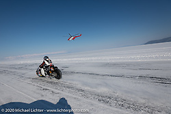 Sebastien Lorentz of Lucky Cats Garage in Chartres, France piloting Belgian custom bike builder Brice Hennebert's 2018 Indian Scout Bobber as he charges down the one-mile ice track one-on-one against a helicopter at the Baikal Mile Ice Speed Festival. Maksimiha, Siberia, Russia. Friday, February 28, 2020. Photography ©2020 Michael Lichter.