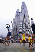 Malaysians in Kuala Lumpur playing volleyball by the Petronas Towers.