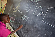 A child from K3 works out a math question on the blackboard. Children attend the kindergarten school to learn a variety of subjects during lessons at the Wema Centre, Mombassa, Kenya.