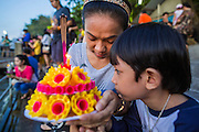 """17 NOVEMBER 2013 - BANGKOK, THAILAND: A mother and her son pray before floating their krathong in the Chao Phraya River at Wat Yannawa on Loy Krathong in Bangkok. Loy Krathong (also written as Loi Krathong) is celebrated annually throughout Thailand and certain parts of Laos and Burma (in Shan State). The name could be translated """"Floating Crown"""" or """"Floating Decoration"""" and comes from the tradition of making buoyant decorations which are then floated on a river. Loi Krathong takes place on the evening of the full moon of the 12th month in the traditional and they do this all evening on the 12th month Thai lunar calendar. In the western calendar this usually falls in November. The candle venerates the Buddha with light, while the krathong's floating symbolizes letting go of all one's hatred, anger, and defilements       PHOTO BY JACK KURTZ"""