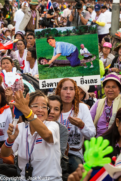 "13 JANUARY 2014 - BANGKOK, THAILAND: An anti-government protestor in Lumpini Park holds up a caricature of former Prime Minister Thaksin Shinawatra riding his sister, current Prime Minister Yingluck Shinawatra, who is portrayed as having the body of a monitor lizard. It is considered a great insult to be portrayed as a monitor lizard in Thailand. Tens of thousands of Thai anti-government protestors took to the streets of Bangkok Monday to shut down the Thai capitol. The protest was called ""Shutdown Bangkok"" and is expected to last at least a week. The Shutdown Bangkok protest is a continuation of protests that started in early November. There have been shootings almost every night at different protests sites around Bangkok, including two Sunday night, but the protests Monday were peaceful. The malls in Bangkok stayed open Monday but many other businesses closed for the day and mass transit was swamped with both protestors and people who had to use mass transit because the roads were blocked.    PHOTO BY JACK KURTZ"
