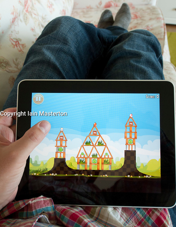 Man playing Angry Birds game on an iPad touch screen tablet computer