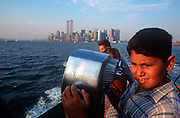 A young 1990s boy looks over the Upper New York Bay during the short Staten Island ferry crossing towards Manhattan where the Twin Towers rise above the skyline before their destruction 2 years later, on 31st July 1998, in New York, USA.