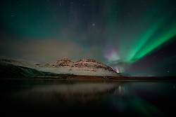 Aurora Borealis, the Northern Lights, over a hillside on the west coast of Iceland.
