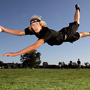 """Members of the Ultimate Frisbee team demonstrate their leaping ability at the University of California, Santa Barbara. The players often perform acrobatic leaps to snare the disc. The team is called the """"Black Tide"""" and are known for being one of the best ultimate frisbee teams in the nation."""