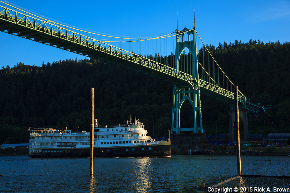 USA, Oregon, Portland, Cathedral Park, a boat on the Willamette River, passing under the St. John's Bridge.