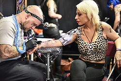 © licensed to London News Pictures. 26/09/2014<br /> The 10th London International Tattoo Convention, one of the most prestigious body art conventions in the world, brought together 400 of the best tattoo artists to thousands of admirers at Tobacco Dock. Other attractions and alternative performances included burlesque, sword swallowing, striptease dancers, fire-dancers and trapeze performers. Pictured. A woman has Iggy Pop tattooed on her arm.<br /> Photo credit : Ian Whittaker/LNP