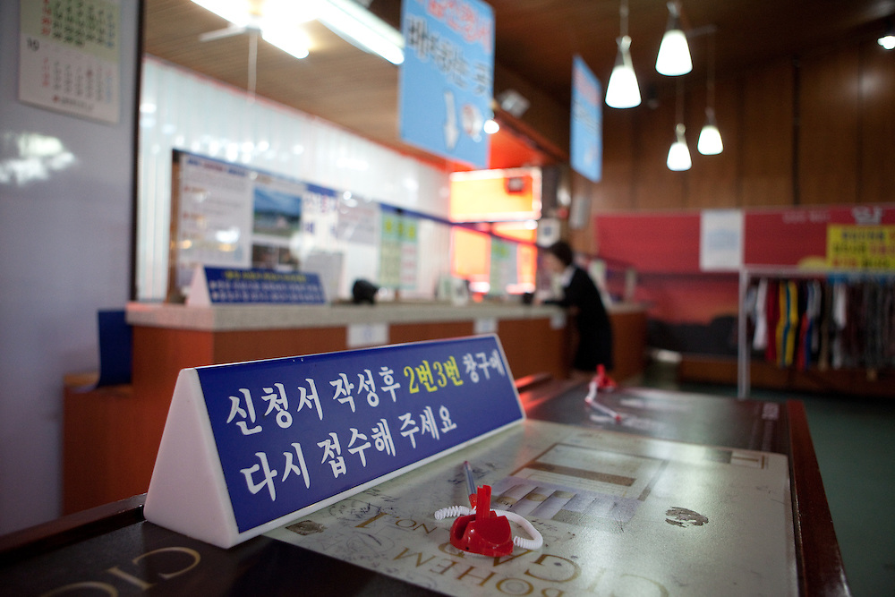Daejin Education Centre hall with information table for filling in entry permit forms and registry counters selling entry tickets for DMZ observatoty / Daejin, South Korea, Republic of Korea, KOR, 08 October 2009.