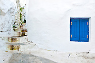 A bright blue windows contrasts with a white wall in Athens, Greece.