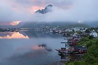 Misty clouds drift across Osltind mountain peak at midnight, Reine, Moskenesøy, Lofoten Islands, Norway