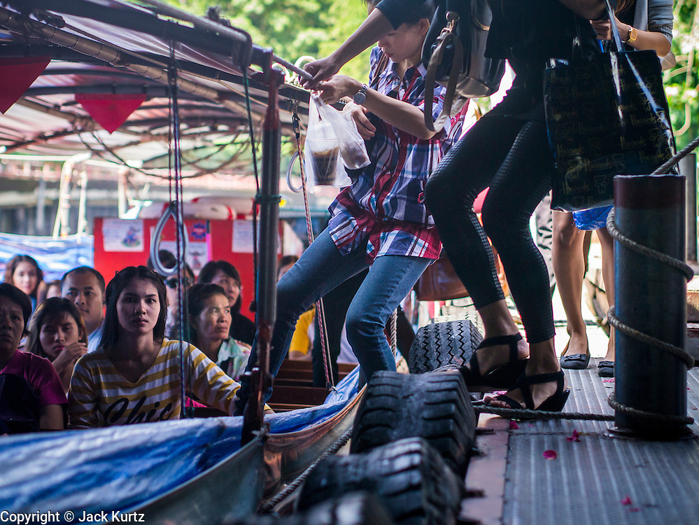 10 OCTOBER 2012 - BANGKOK, THAILAND:  Passengers move to get on a fast passenger boat on Khlong Saen Saeb at the AsokPetchaburi Pier in Bangkok. Bangkok used to be criss crossed by canals (called Khlongs in Thai) but most have been filled in and paved over. Khlong Saen Saeb is one of the few remaining khlongs in Bangkok with regular passenger boat service. Boats and ships play an important in daily life in Bangkok. Thousands of people commute to work daily on the Chao Phraya Express Boats and fast boats that ply Khlong Saen Saeb. Boats are used to haul commodities through the city to deep water ports for export.     PHOTO BY JACK KURTZ