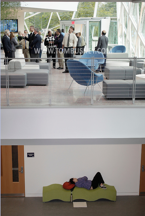 A person rests on a couch downstairs as people above enjoy the grand opening of the Atrium at SUNY New Paltz on Monday, Sept. 13, 2010.