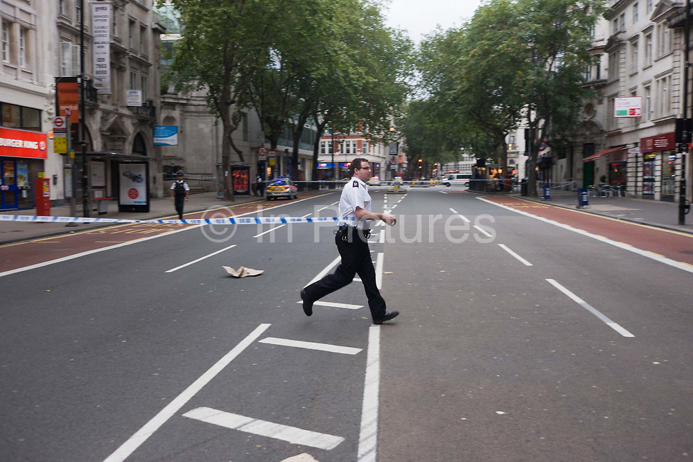 Suspect packages have been found outside premises in Central London, a situation urgent enough to warrant the closure of Holborn and surrounding streets in case the items are terrorist-related. The subsequent evacuation of commuters at a time when thousands of office workers were making their way out of their company buildings towards the London Underground station ahead on the right. A police officer runs across the road stretching a length of police tape barring anyone from crossing. The force are taking no chances from abandoned rubbish left at will in public places - their efforts that may save lives from explosive terrorist devices, such as bombs. With streets emptied during the busiest time of the day, the police have control of the area while around the corner, experts inspect the problem before re-opening to the public.