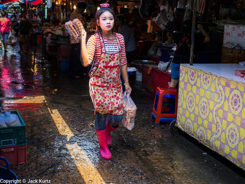 """03 APRIL 2014 - BANGKOK, THAILAND:   A  vendor walks through Khlong Toey Market in Bangkok. Khlong Toey (also called Khlong Toei) Market is one of the largest """"wet markets"""" in Thailand. The market is located in the midst of one of Bangkok's largest slum areas and close to the city's original deep water port. Thousands of people live in the neighboring slum area. Thousands more shop in the sprawling market for fresh fruits and vegetables as well meat, fish and poultry.     PHOTO BY JACK KURTZ"""