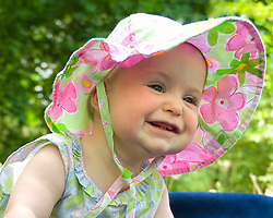 Sarah, Linda and Kate came to visit Mom on May 26, 2007. Here she played in the front yard on a blue blanket. Smiling baby in a bonnet.